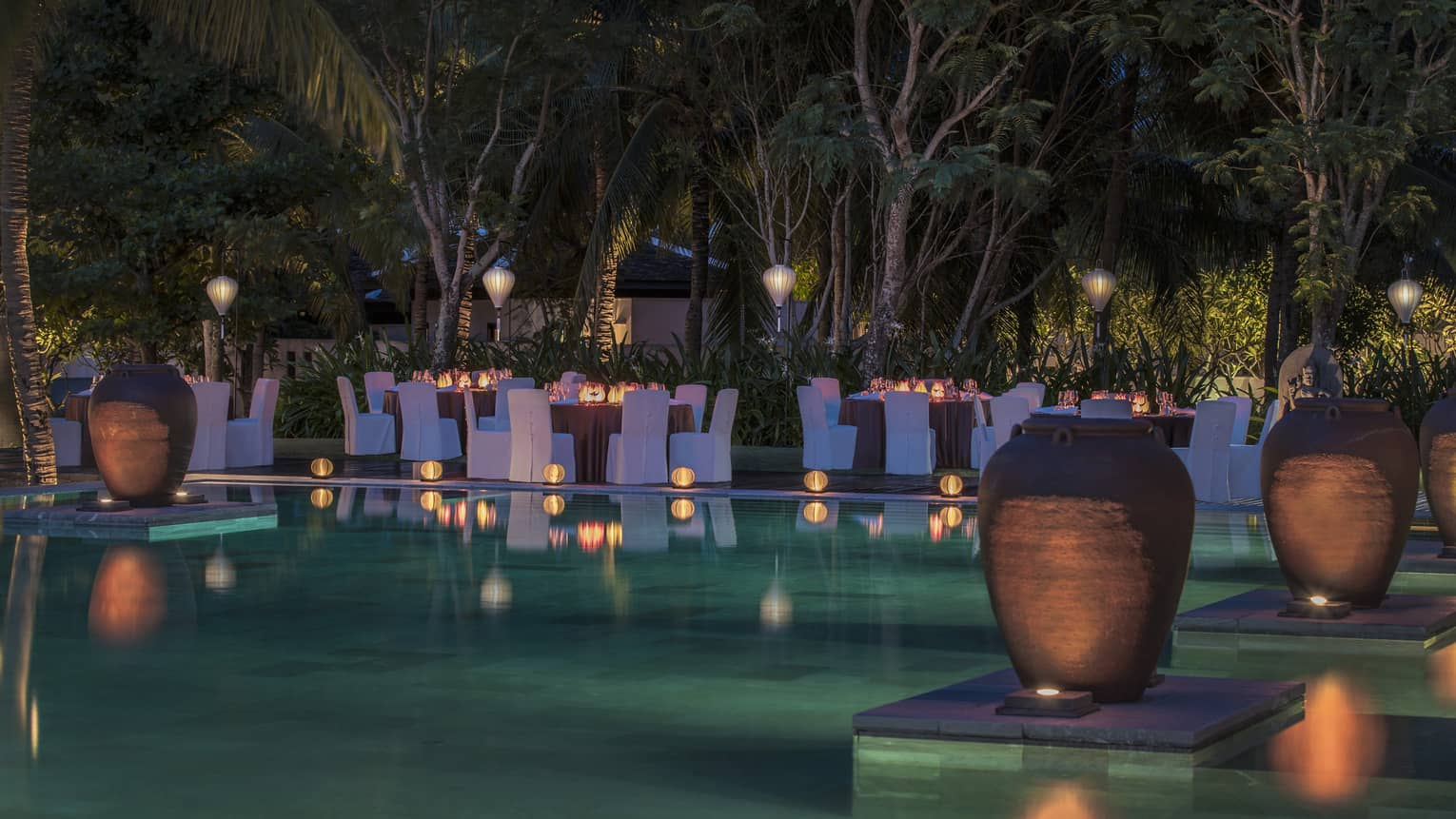 Tables and chairs with blue covers surround pool at night, surrounded by lanterns and vases