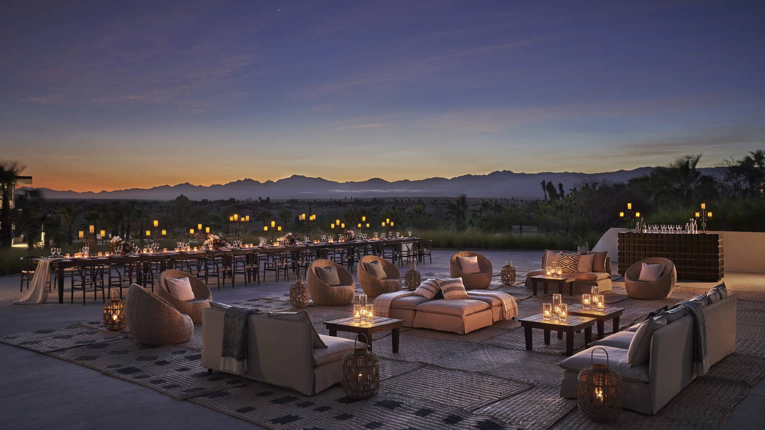 The sky is dark at dusk while the terrace is set with white couches and low tables decorated with candles and a long banquet style table set off to the side