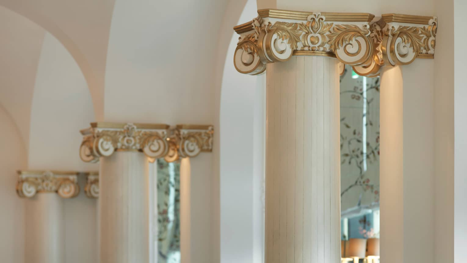 Close-up of top of white pillars with Beaux-Arts style decorative gold detail
