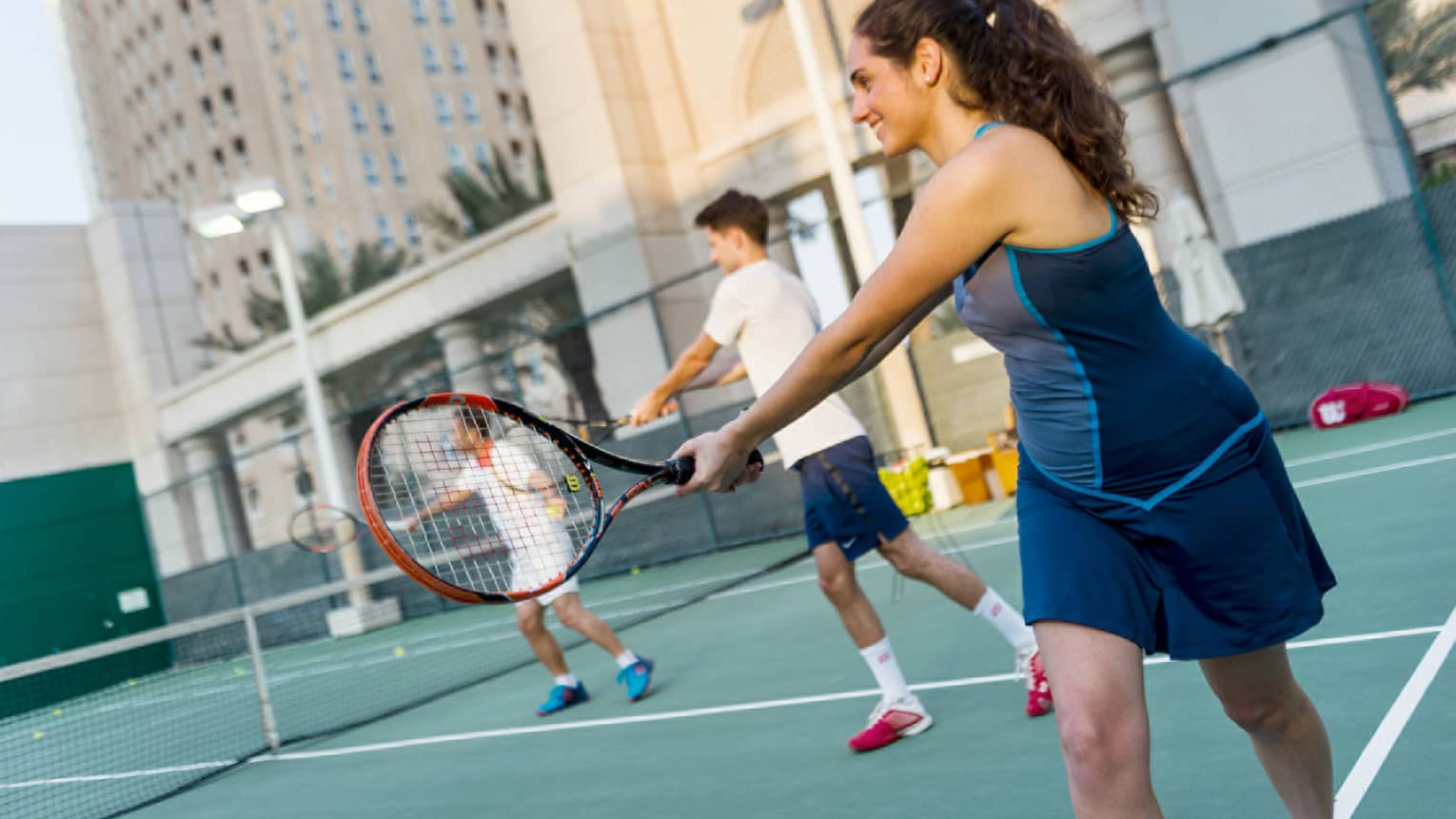 Woman in tennis outfit holds out racket, two people in background on court