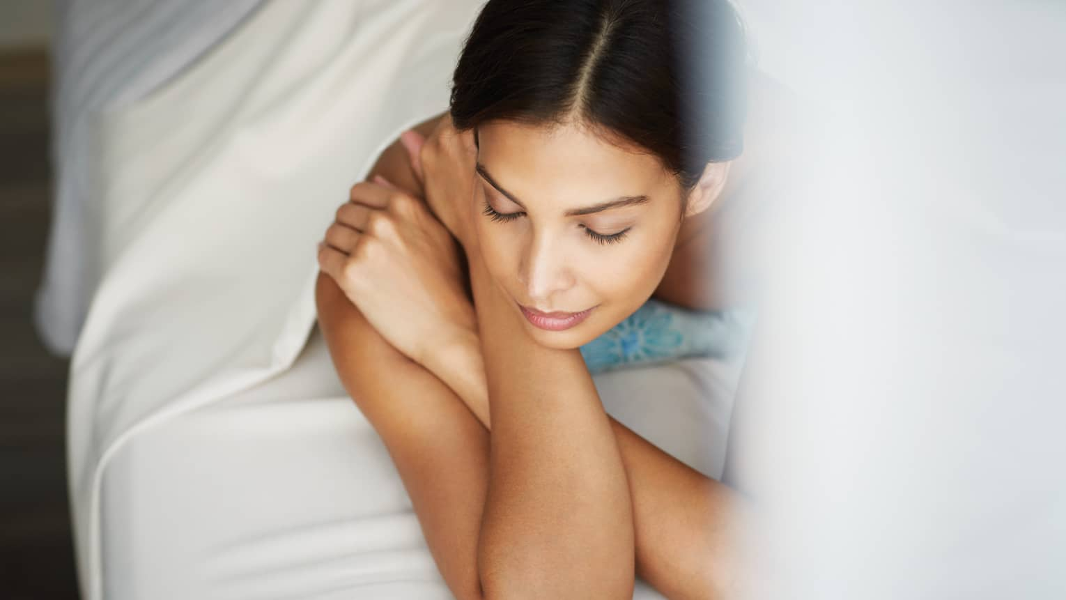 Woman with dark hair lays on her stomach under white sheet, propped up on arms, eyes closed