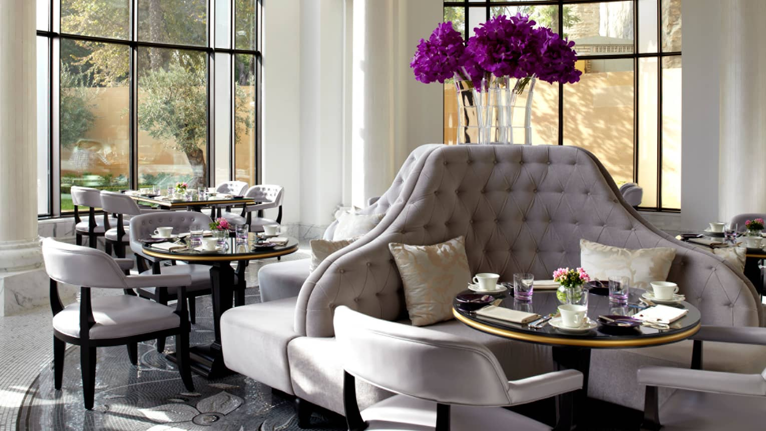 Sunny Zafferano dining room with tall, curved plush grey banquettes with purple flowers in vase above, chairs