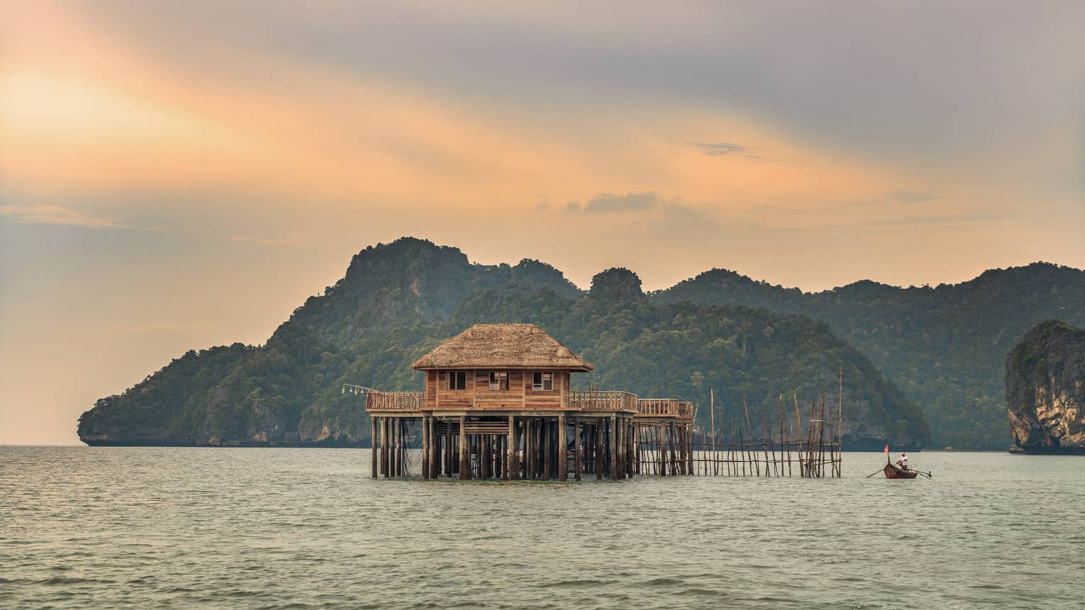 A sunsetting over a lake with huts on it in Langkawi