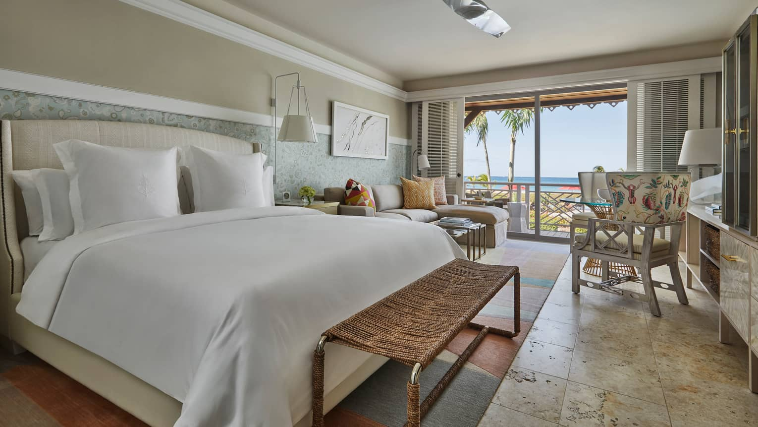 Ocean-View Room bed, wicker bench, chair, sofa by sunny balcony doors, shutters