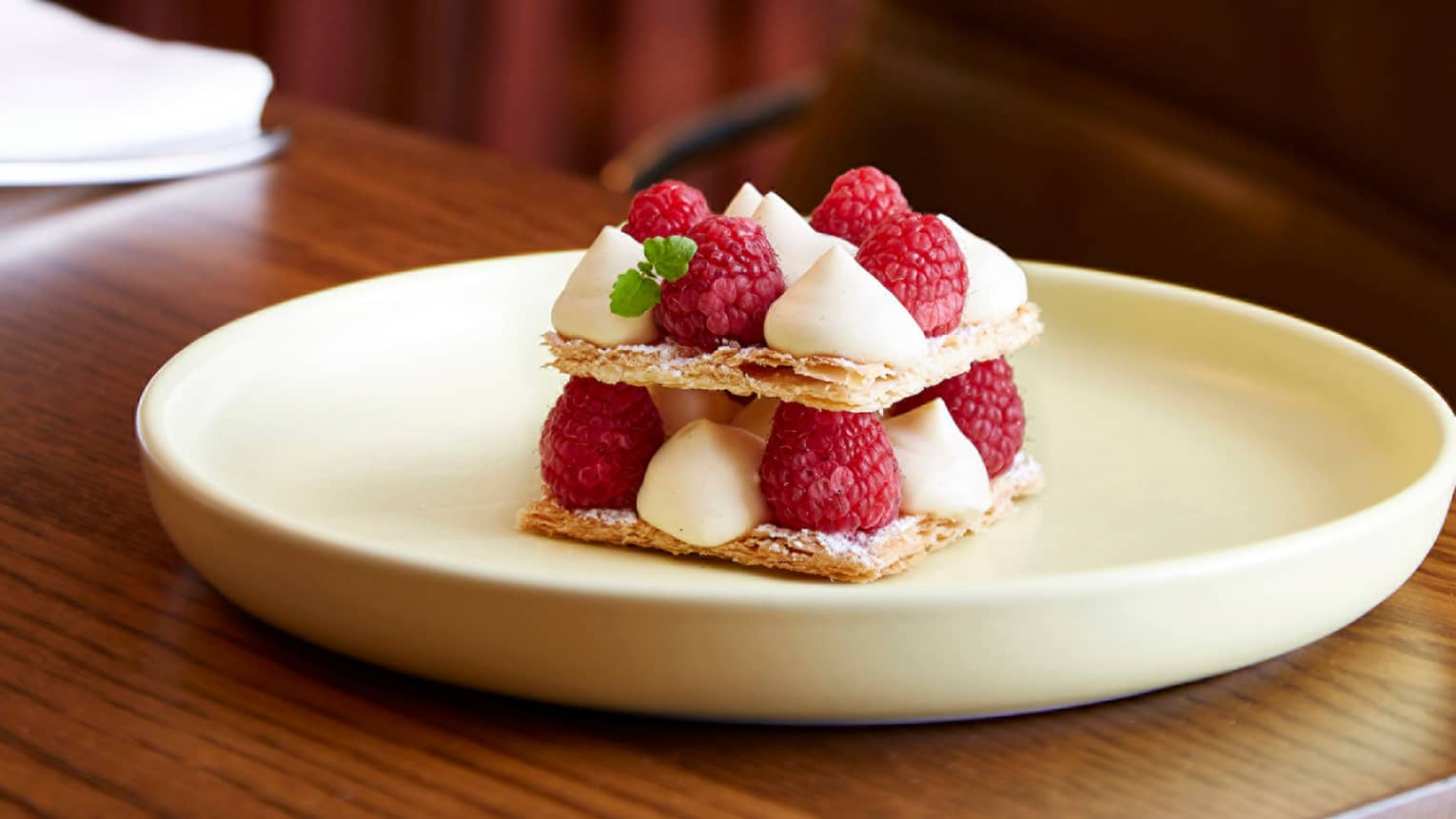Millefeuille custard dessert with chantilly cream, fresh raspberries on plate
