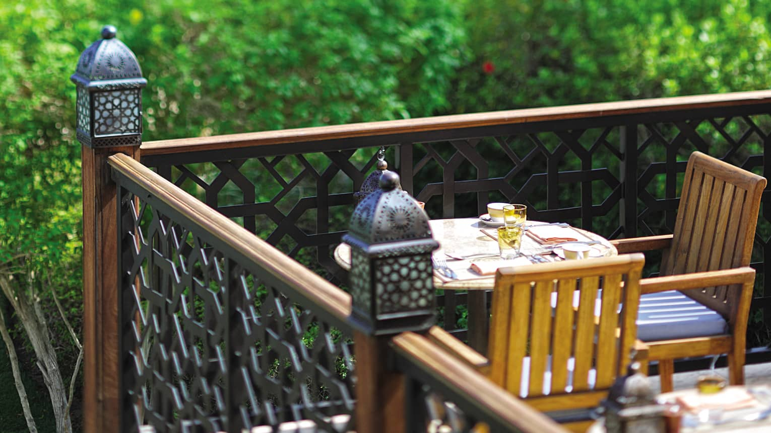 Close-up of small lanterns on wood corner balcony by small cafe table