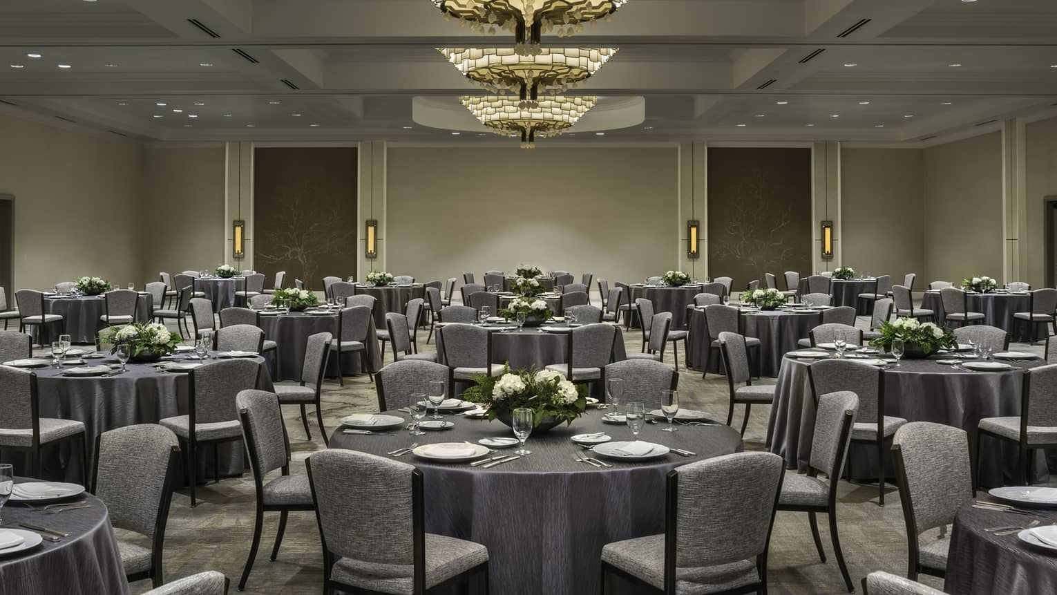Round banquet tables with grey linens, chairs in ballroom
