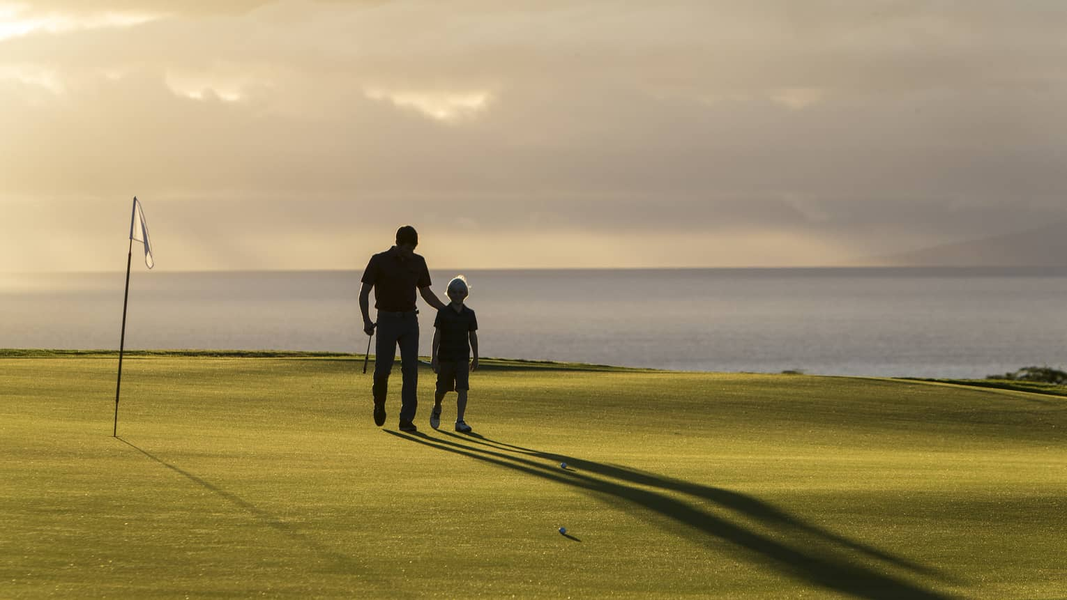 Silhouette of man and boy, flag on pole on golf course green at sunset