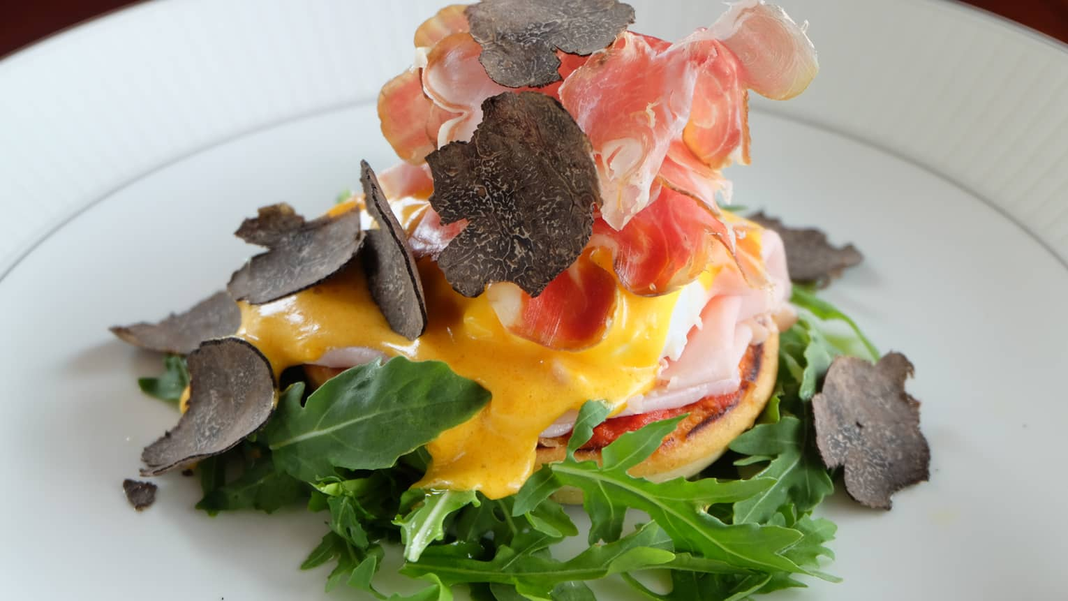 Close-up of eggs Benedict dish topped with yellow sauce, cured meats, crispy roots, lettuce