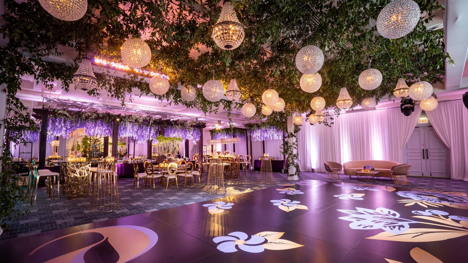 Tables, chairs, and a dance floor, lattice ceiling with green garlands, and crystal chandeliers.