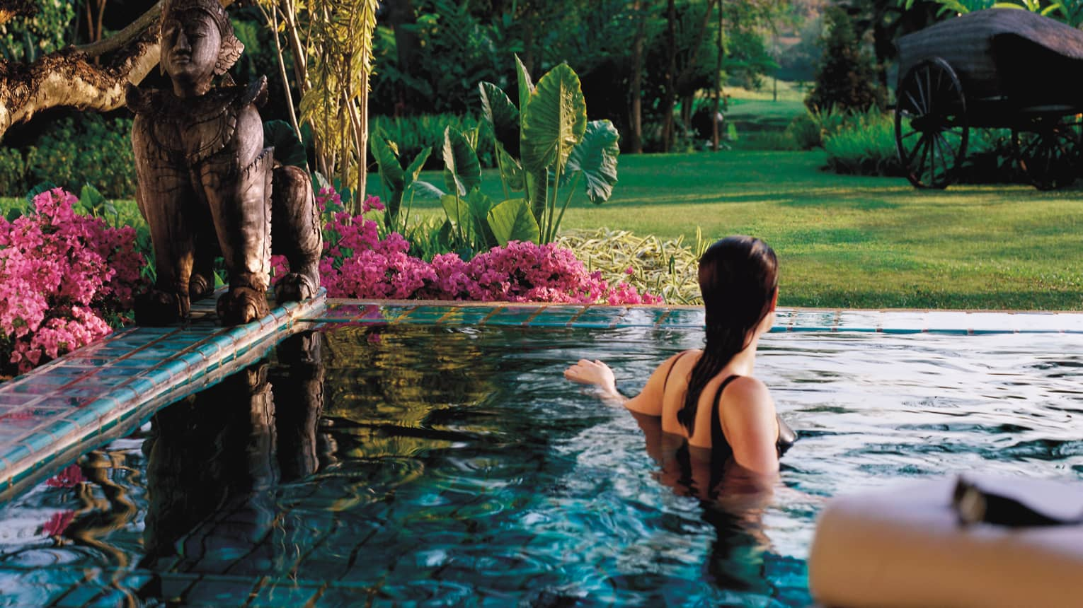 Back of woman in swimsuit wading in private plunge pool lines with pink flowers, large bronze statue