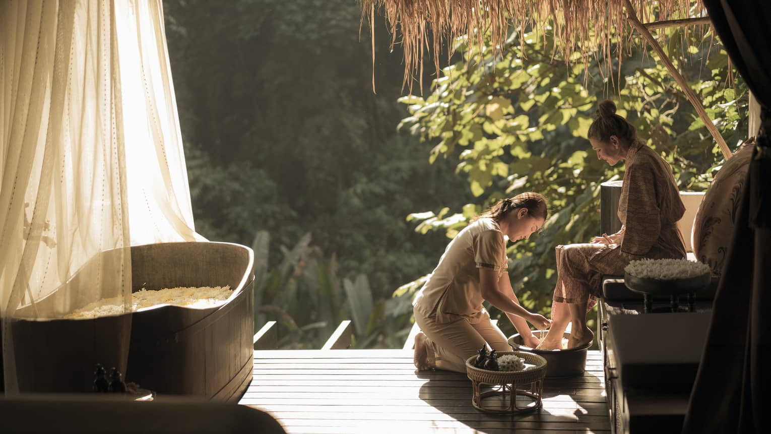 Spa technician kneeling, rinsing feet of woman seated, wearing spa robe under thatched roof