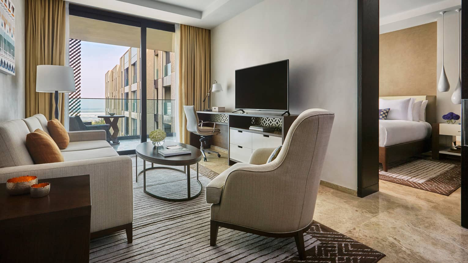 Four Seasons Deluxe Suite modern beige sofa, armchair, TV, large glass door to balcony