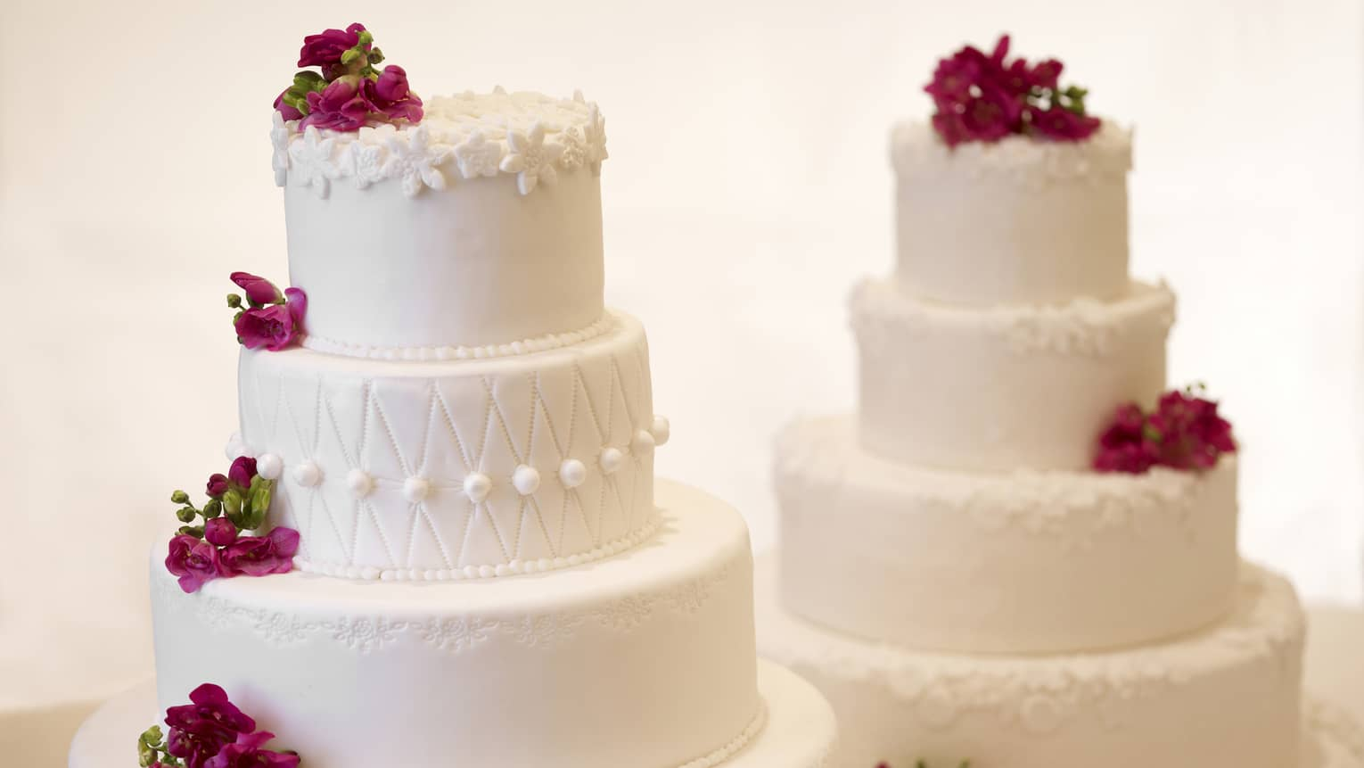 Two white tiered wedding cakes decorated with purple flowers