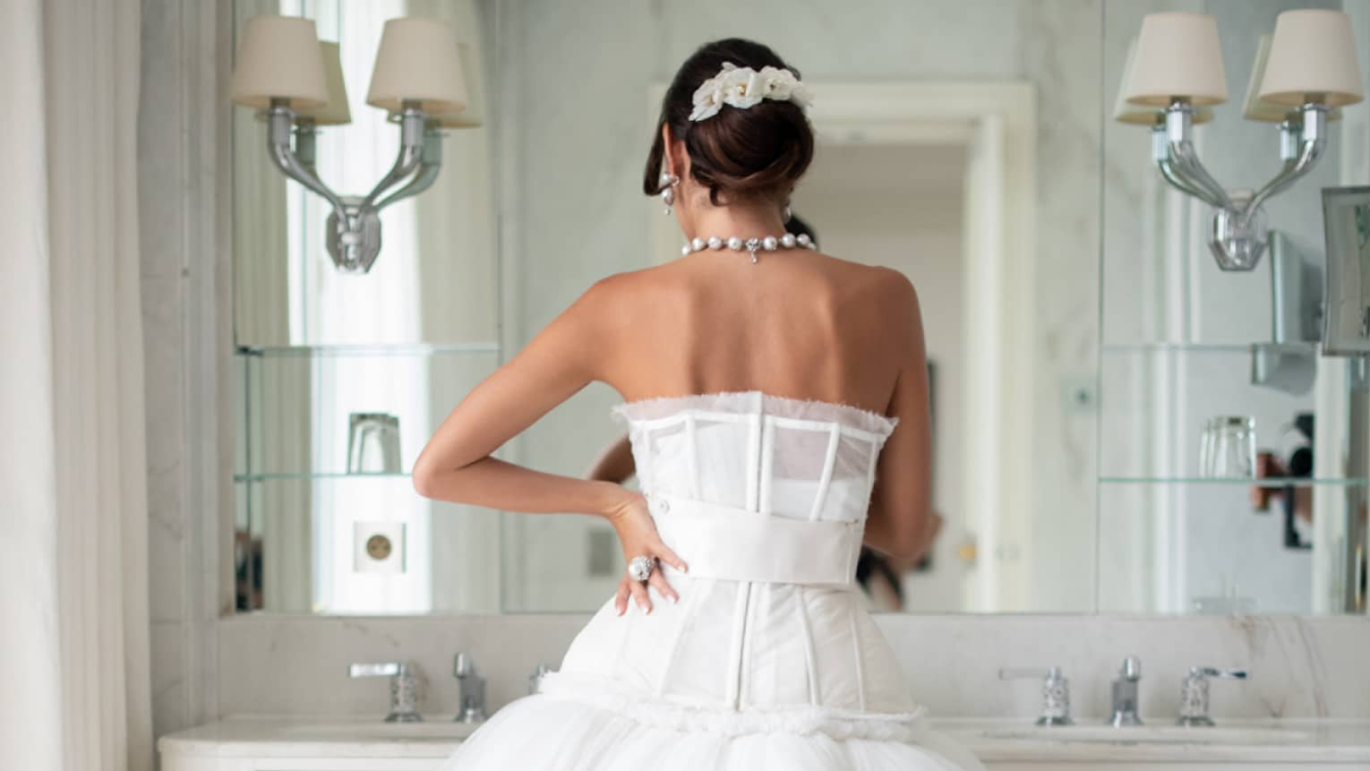Back view of bride standing at vanity mirror in couture strapless wedding gown, hair up, hand on hip