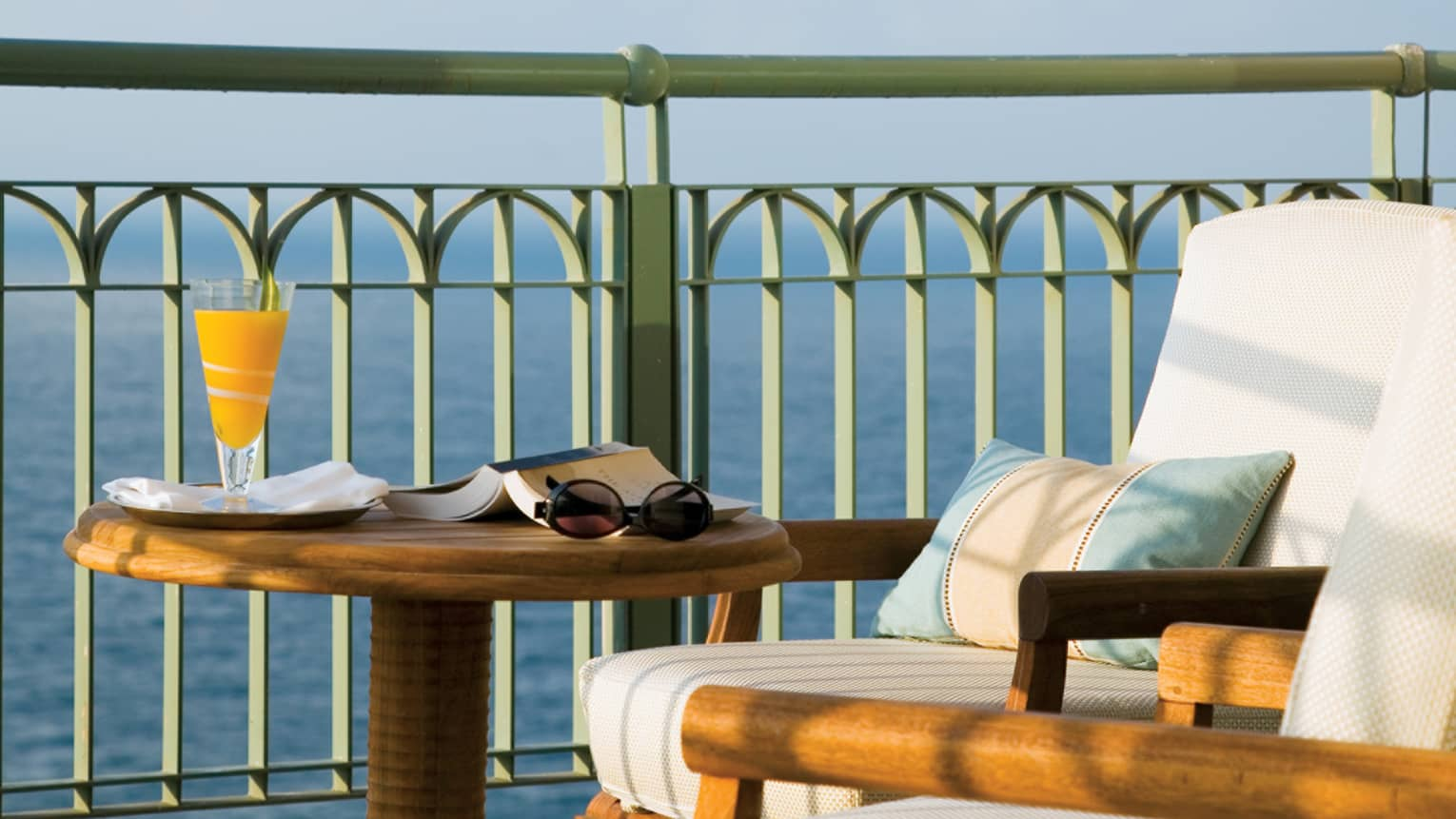 Close-up of Presidential Suite patio round wood table with open book and orange juice, chair cushion, ocean view