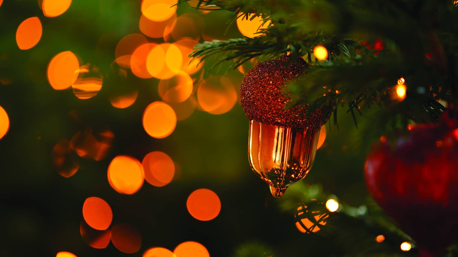 Gold-sparkling acorn and globe ornaments on a Christmas tree branch