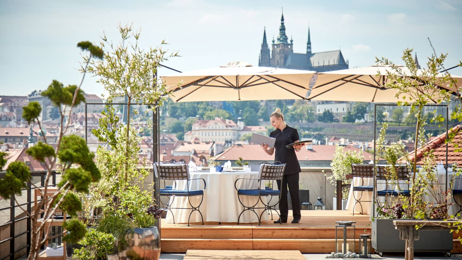 Hotel staff sets dining table under umbrella on rooftop patio overlooking sunny Prague city