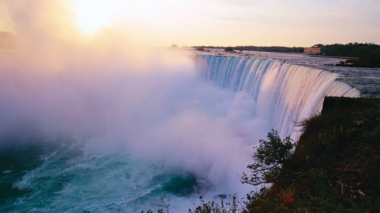 Mist rising from Niagara Falls waterfall at sunrise