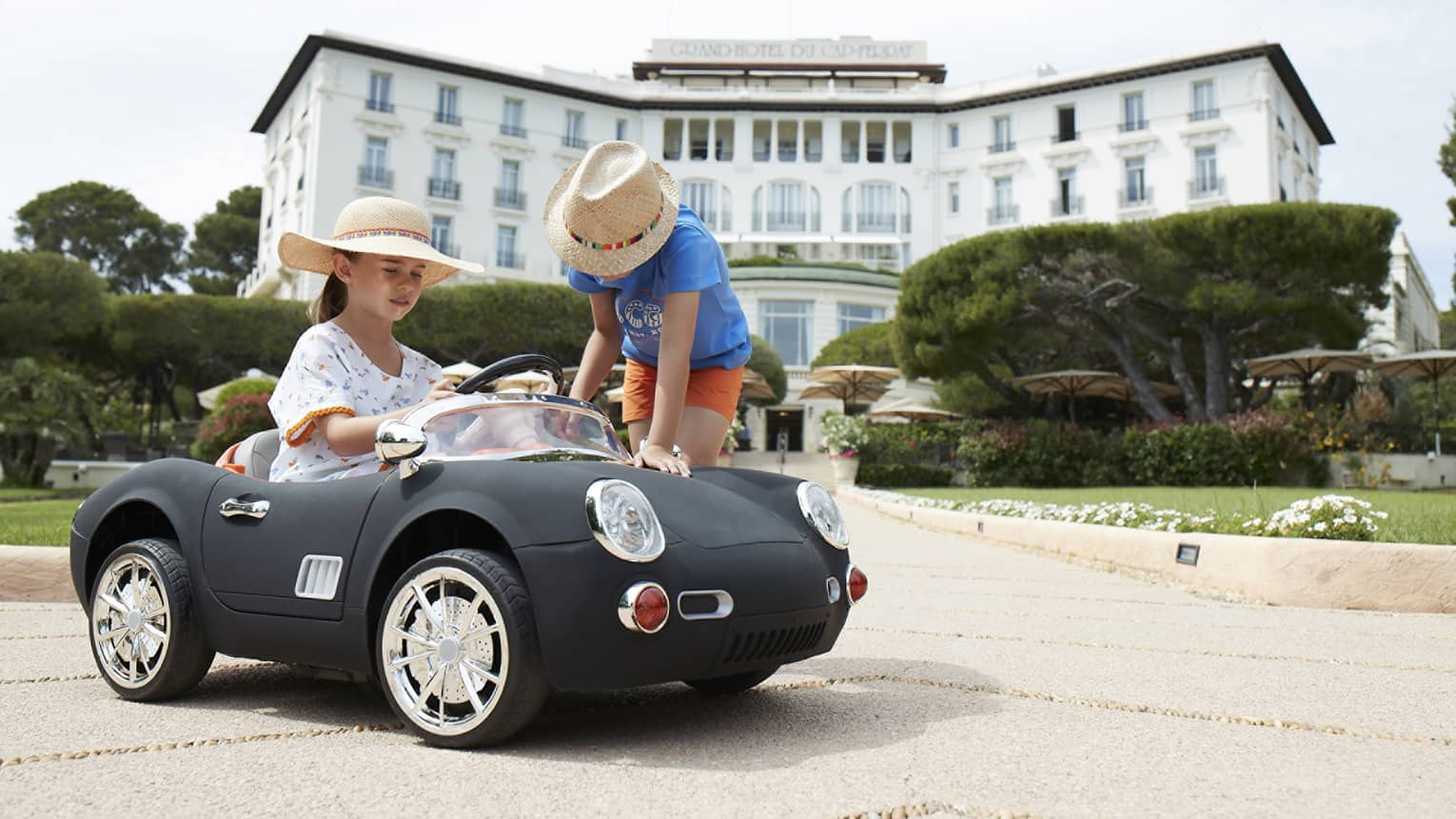 Girl wearing floral dress and straw hat driving black luxury mini convertible, boy in straw hat leaning over, hotel in backdrop