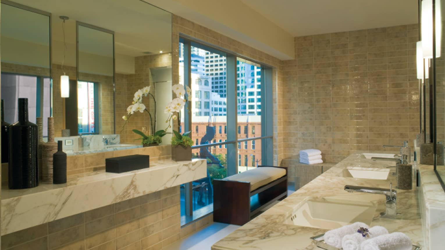 Marble sinks, rolled white towels in front of spa window