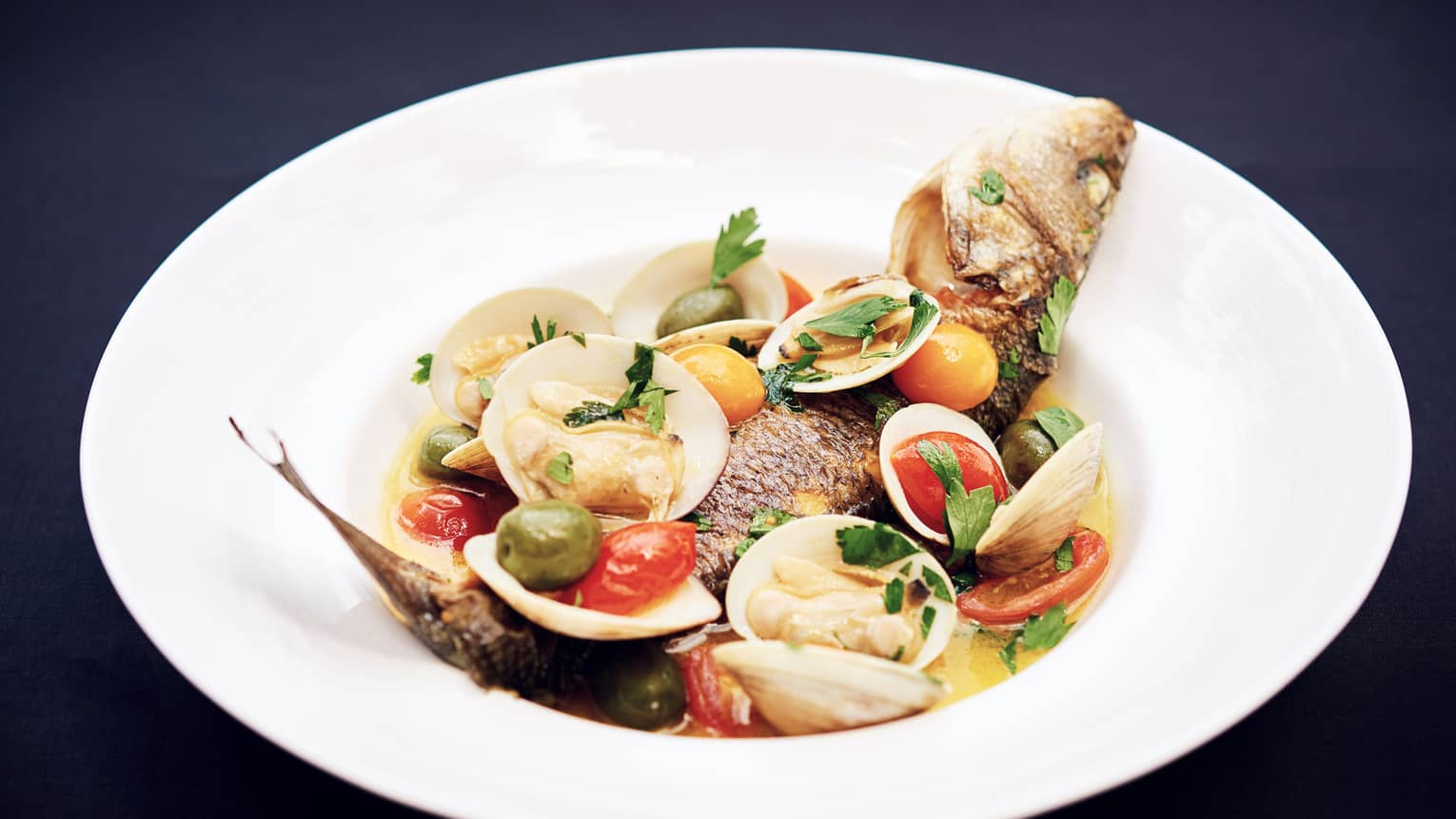 Whole fish with clams, shells, whole olives and tomatoes in bowl