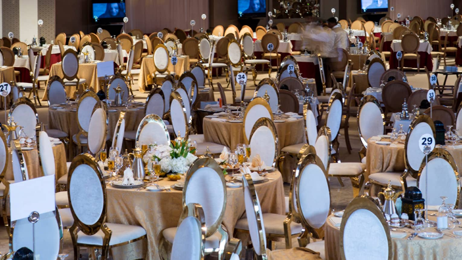 Hotel ballroom dining chairs below tall ceiling where large, elaborate silver lamps and chandeliers hang