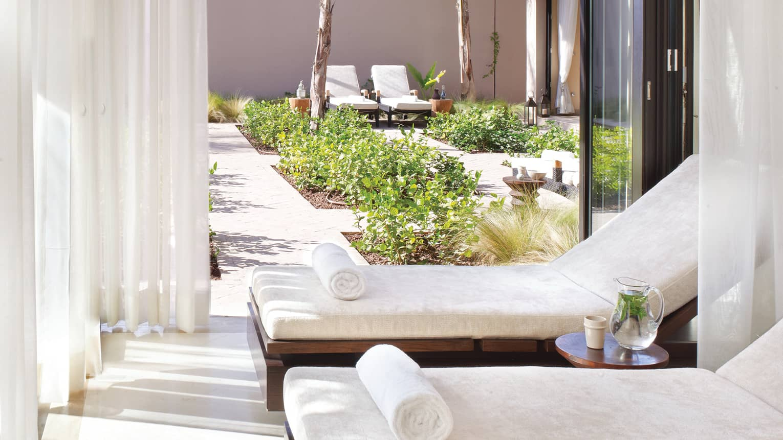 Two white lounge chairs in cabana on spa patio