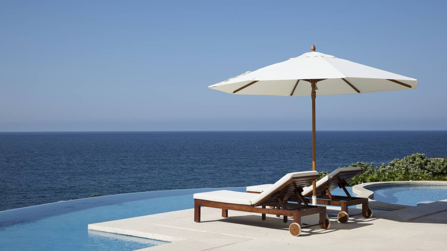 Two lounge chairs under white patio umbrella at edge of infinity pool, ocean views