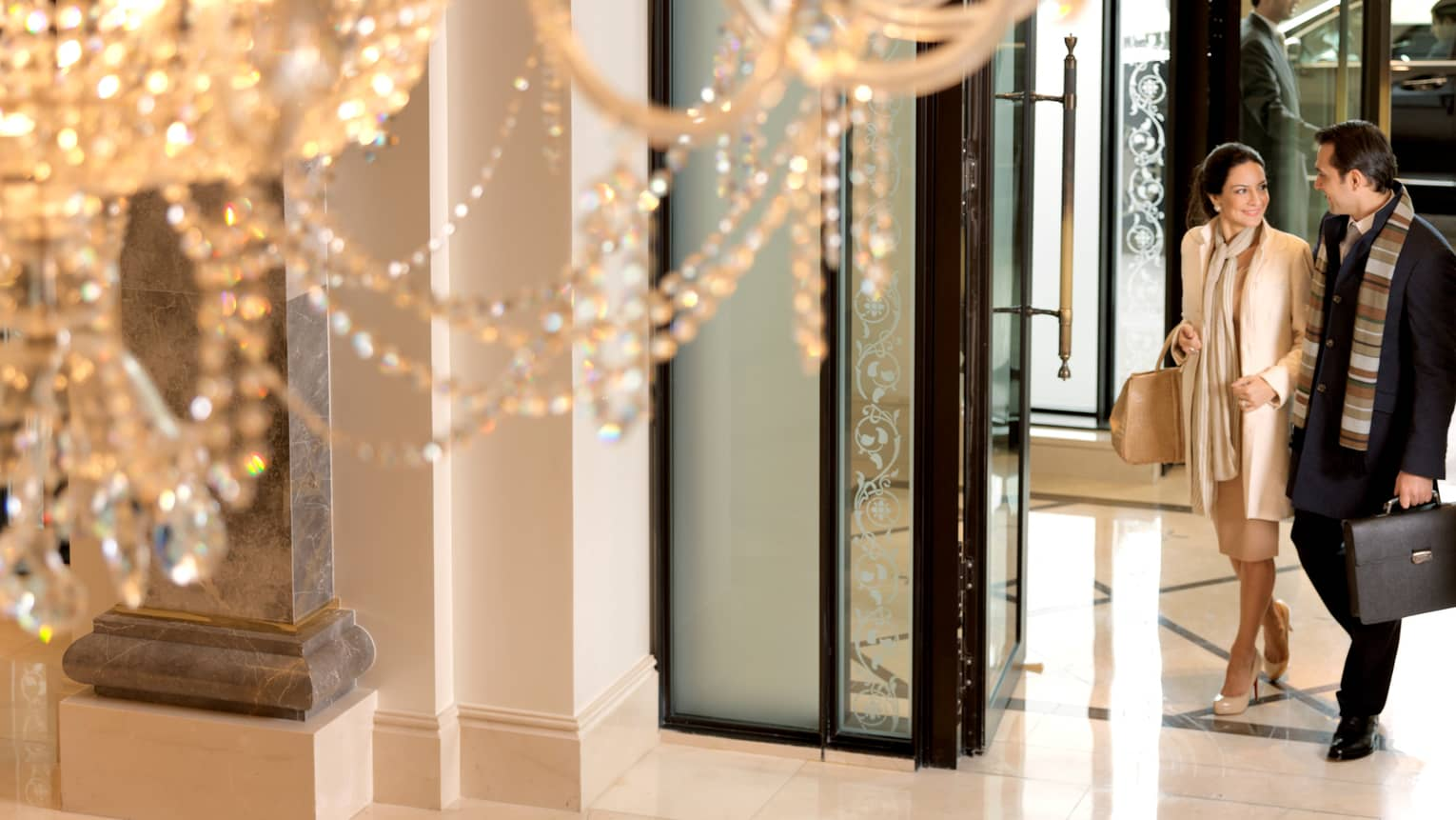 Close-up of crystal chandelier, view below of elegantly-dressed woman linking arms with man, walking in through hotel lobby doors