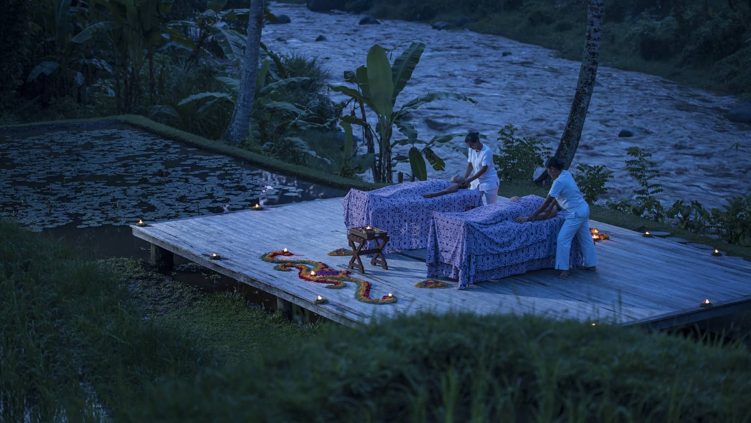 Two guests receive candle-lit massages on a dock at night