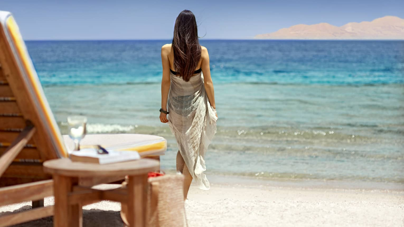 Woman wearing white flowing dress walks away from chair on beach toward sea