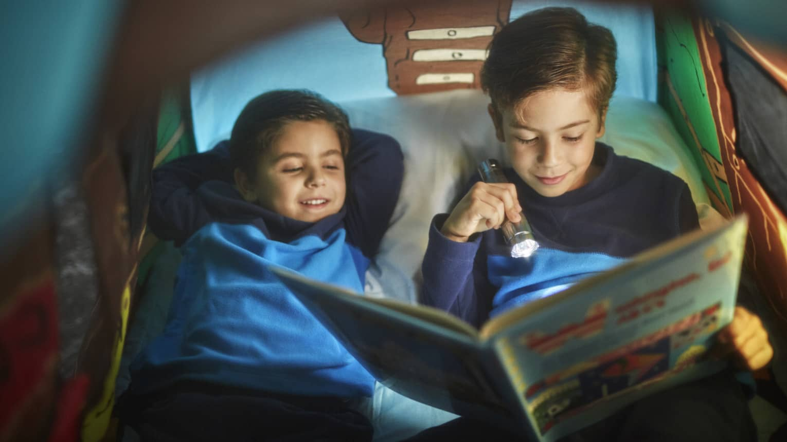 Two little boys in a kids' tent, reading a children's book by flashlight