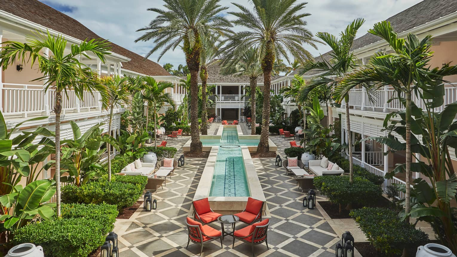 Patio chairs, tables around cross-shaped fountain, large palm trees in Hartford Courtyard