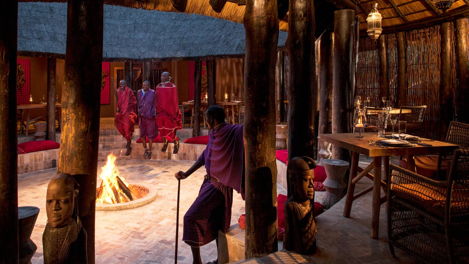 Maasai guides stand around open fire pit in middle of Boma Grill dining hut