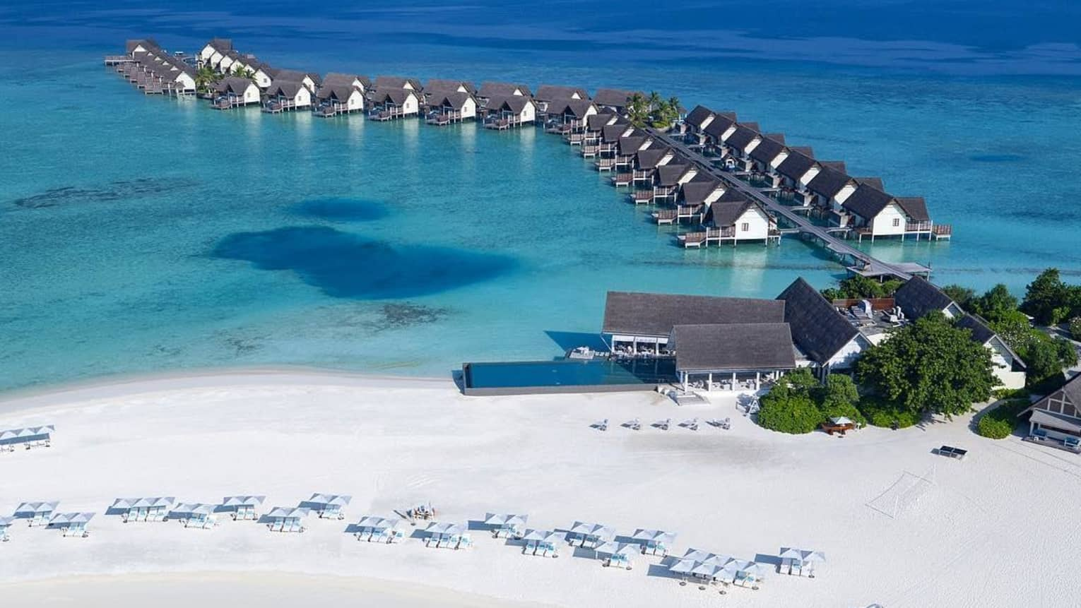 Aerial view of white sand beach, row of overwater bungalow villas stretching over blue lagoon