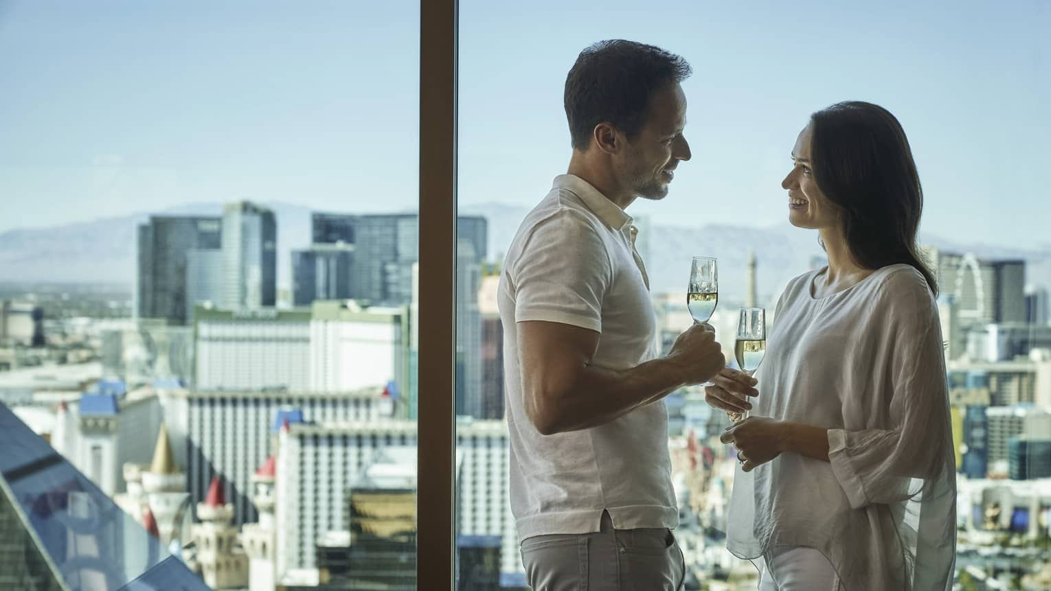 A couple cheers their glasses as they enjoy the view of the city from a floor length window