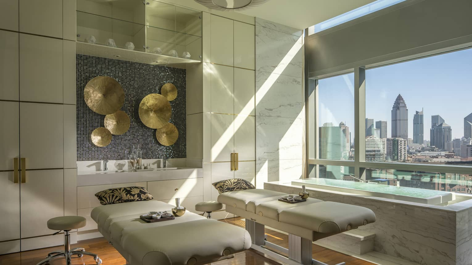 Couples massage beds with pillows under brass disc art on walls in L'Océan Spa