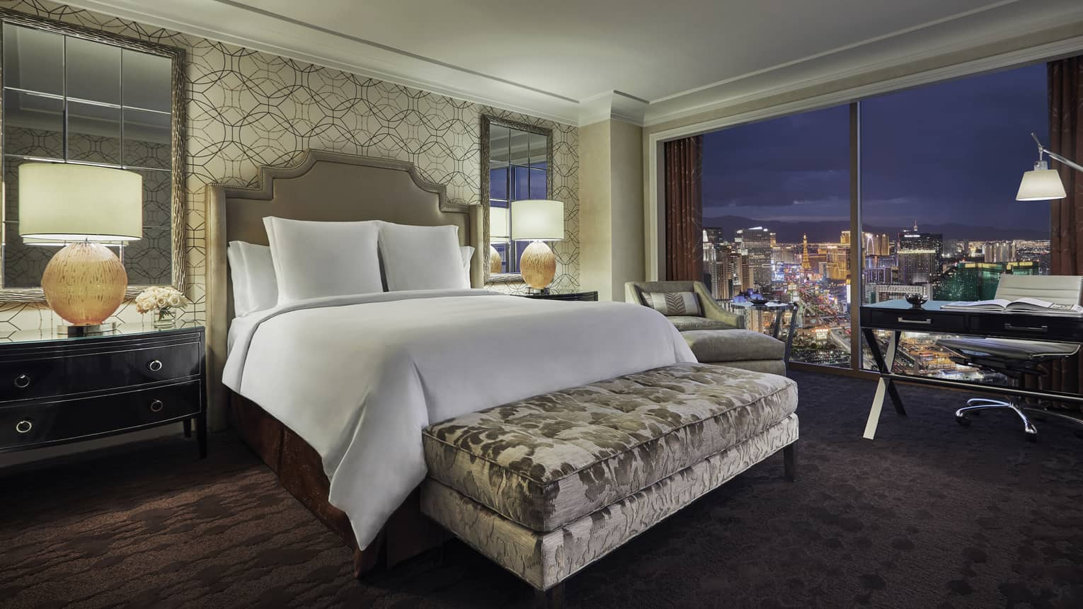 Strip-View Room bed with padded headboard, silver velvet bench, window overlooking Vegas lights at night