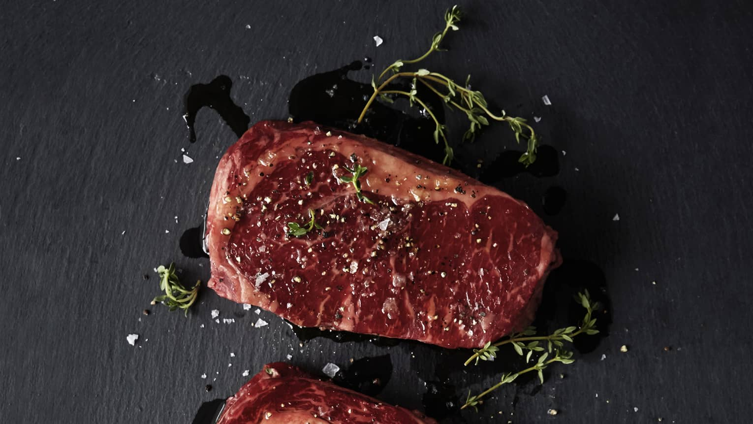 Raw Australian rib-eye steak garnished with salt, pepper, thyme on black counter