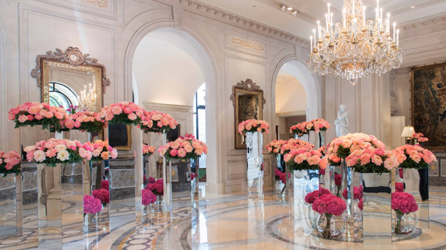 Four Seasons Hotel Paris marble lobby with gleaming floors, large pink floral arrangements
