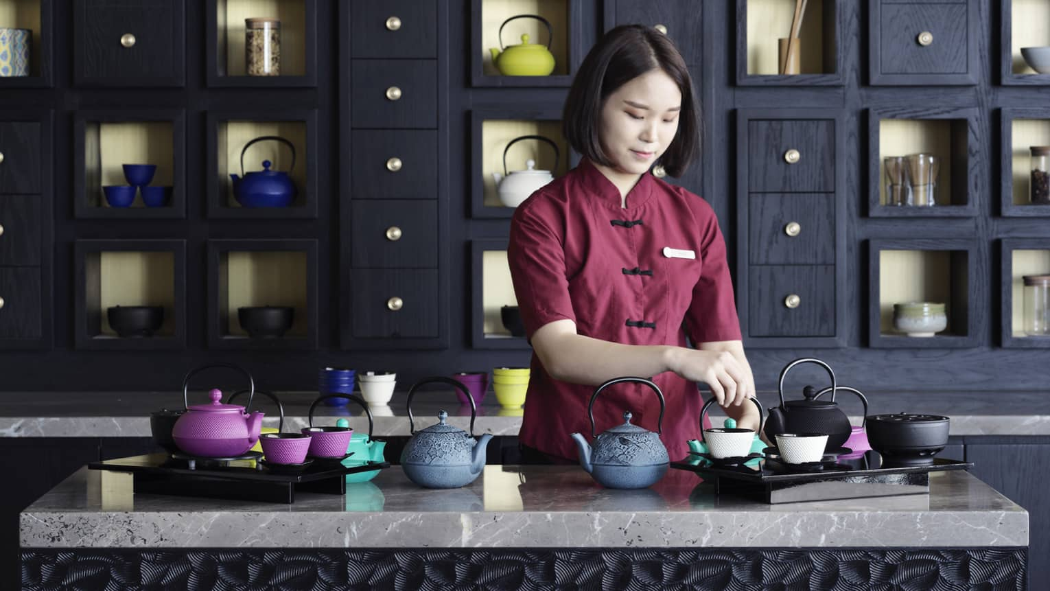Woman in burgundy uniform prepares colourful iron teapots on marble counter