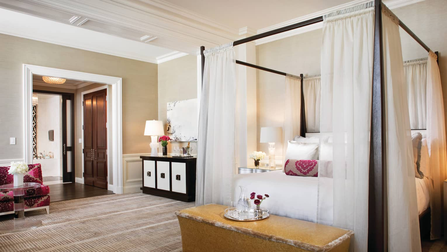 Beverly Wilshire, a Four Seasons Hotel Presidential Suite poster bed with white curtains, velvet bench with tray, water jug, flowers