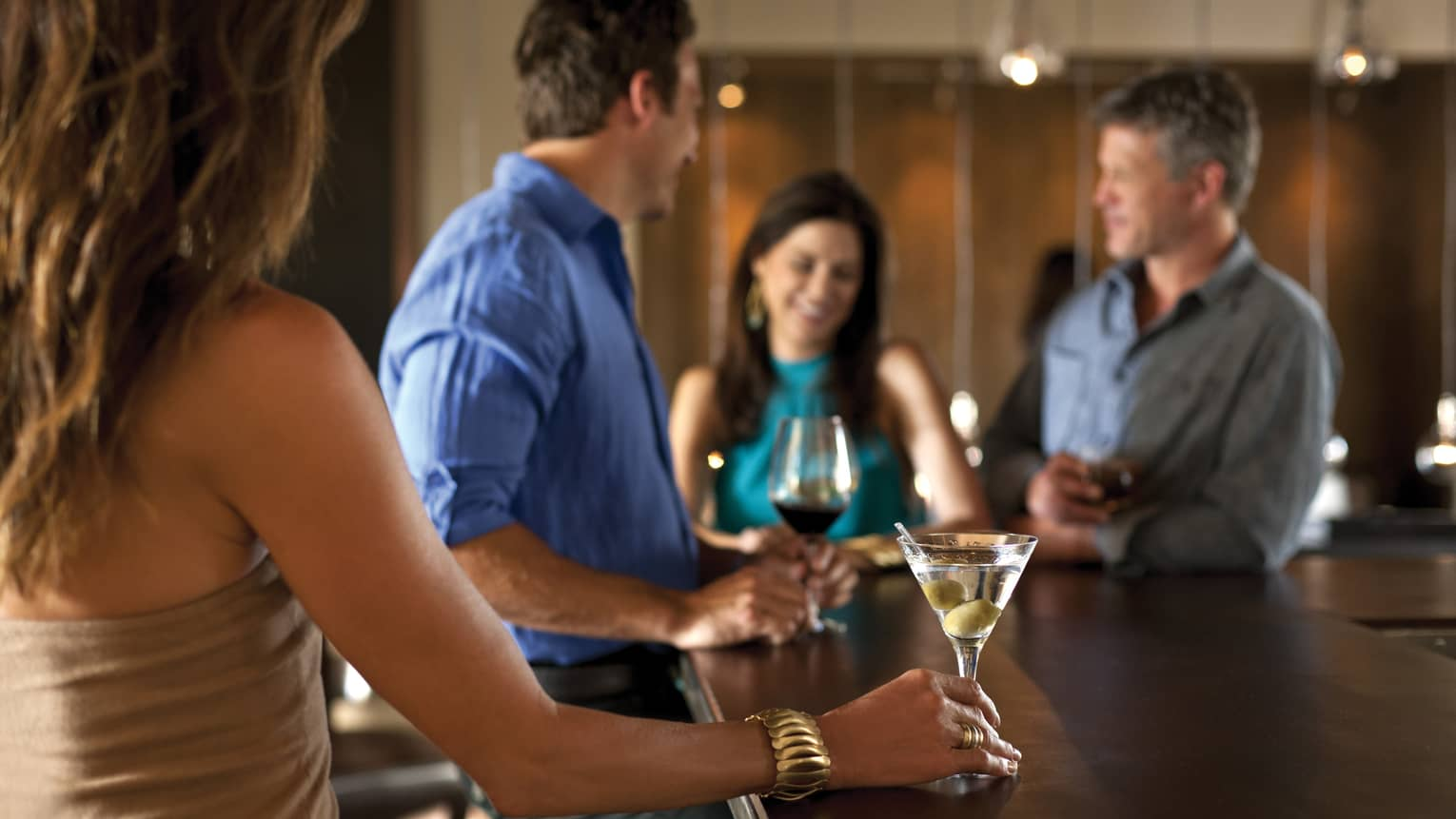 Woman holds martini glass with olives at bar near people with wine
