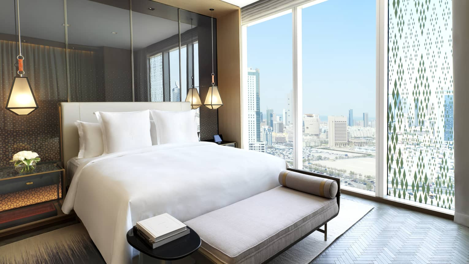Hotel guest room bed, modern hanging lights above nightstands, plush bench, floor-to-ceiling windows