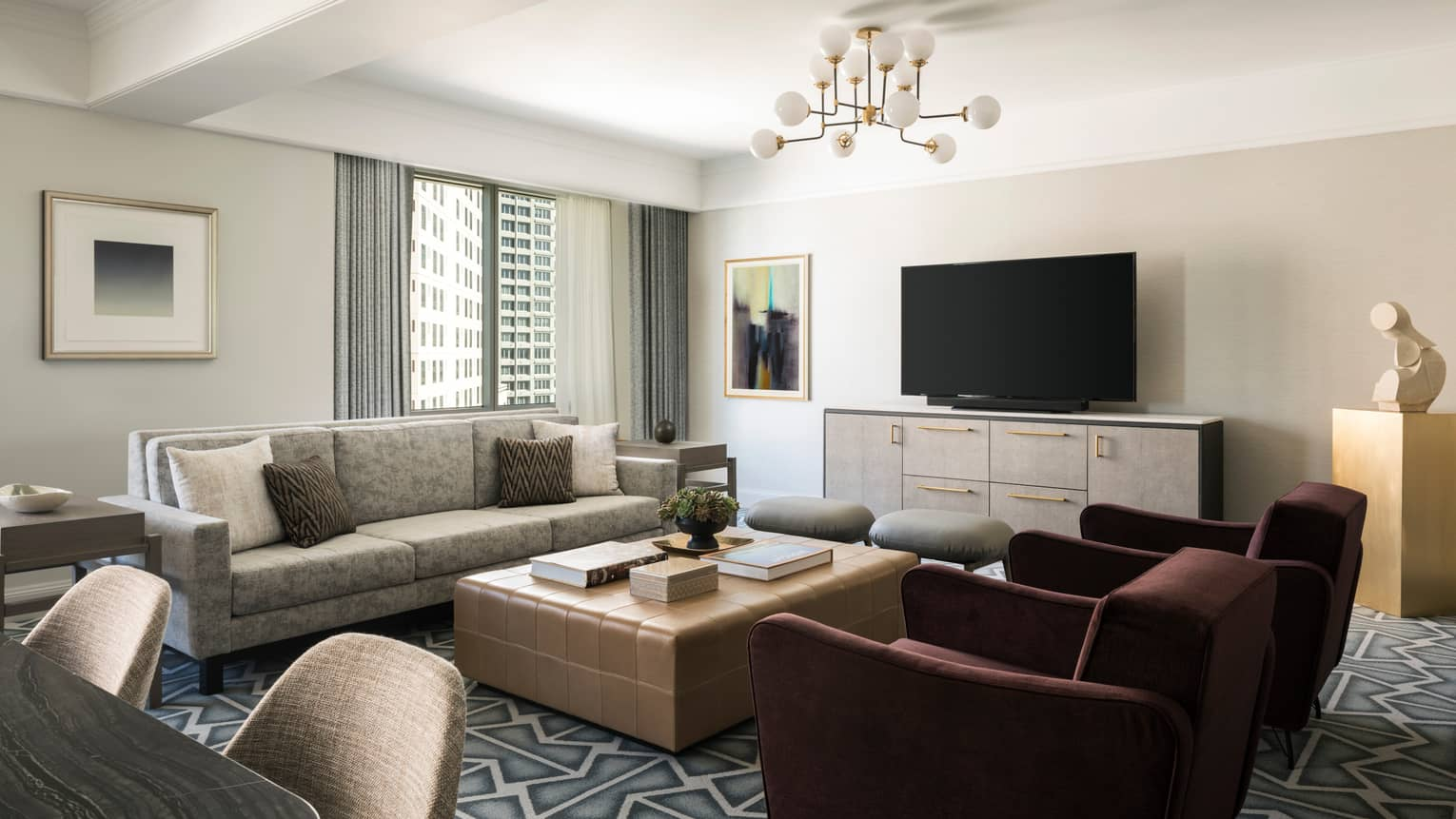 Living room with beige sofa, large square coffee table, two burgundy arm chairs, graphic carpeting