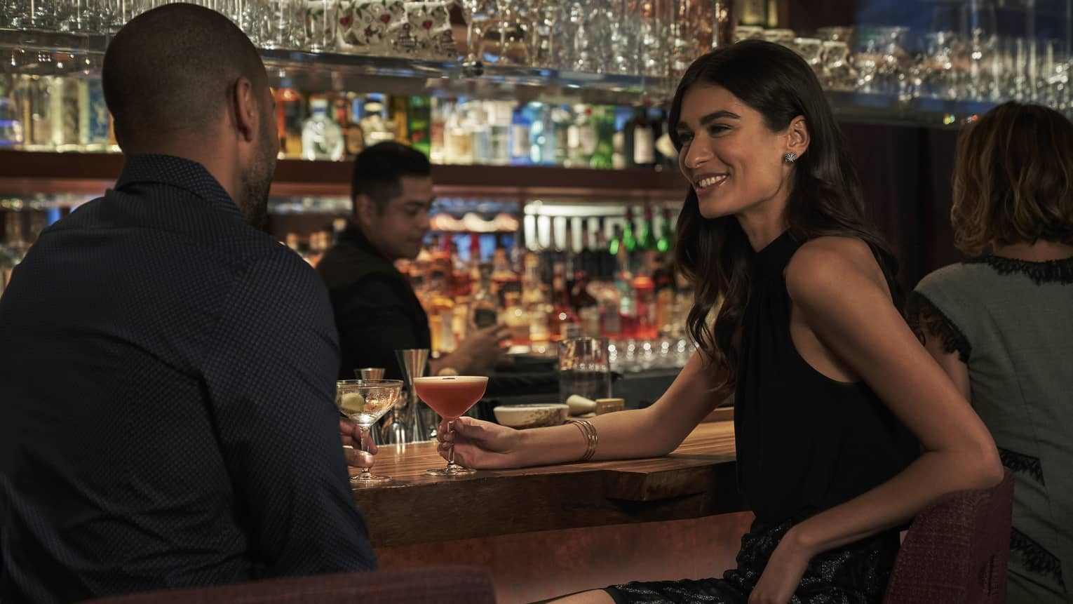 Man and woman with freshly-poured cocktails engage in conversation while sitting at the bar