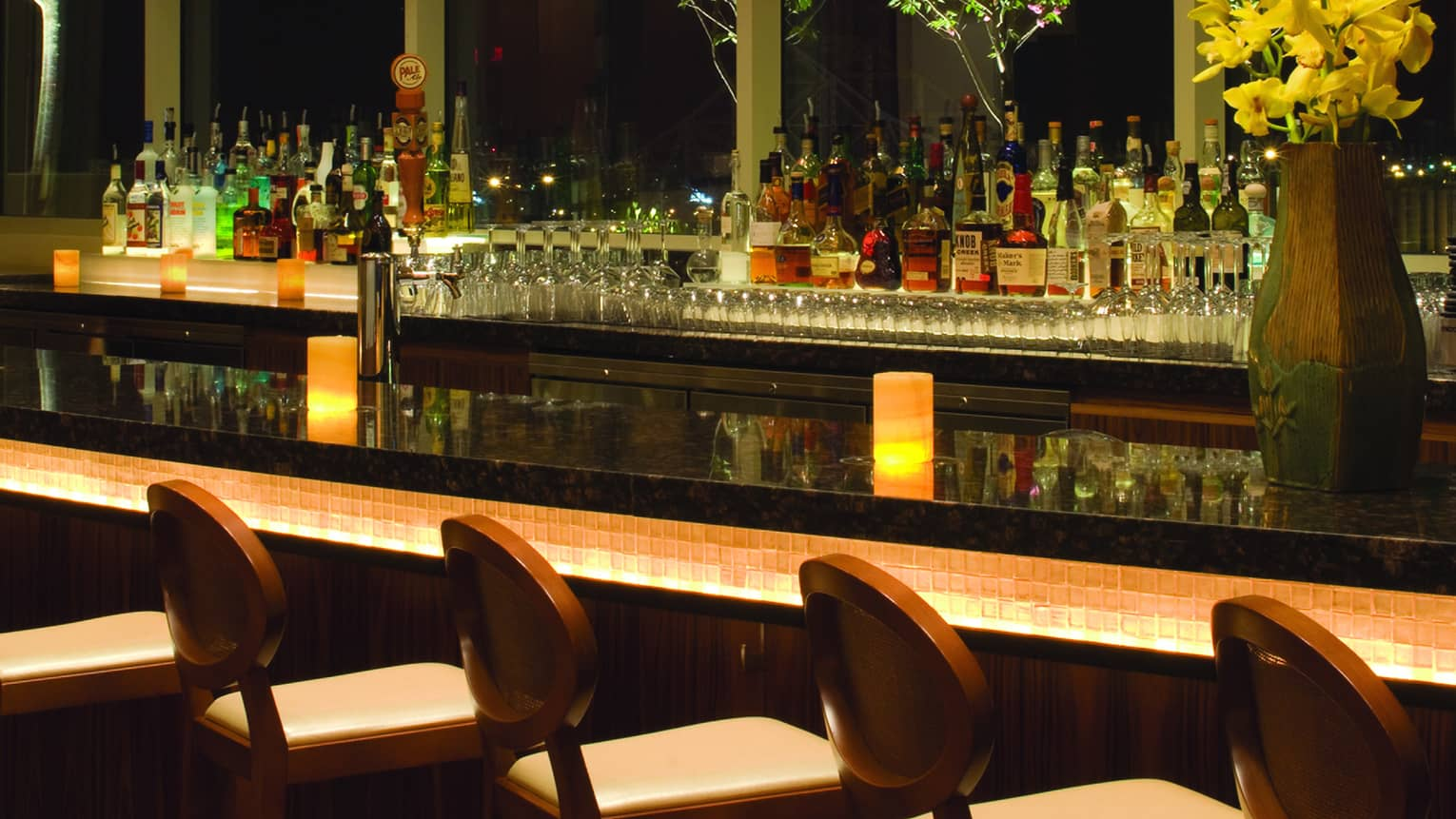 Barstools line black marble Cielo bar at night with glowing candles, wood vase with yellow flowers