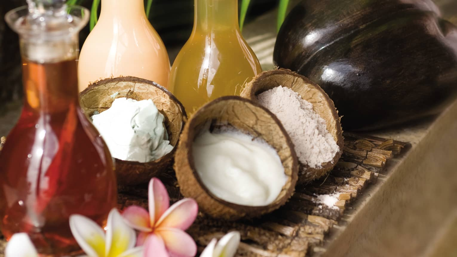 Three open coconut shells filled with white creams and lotions, glass bottles with infused oils, flowers