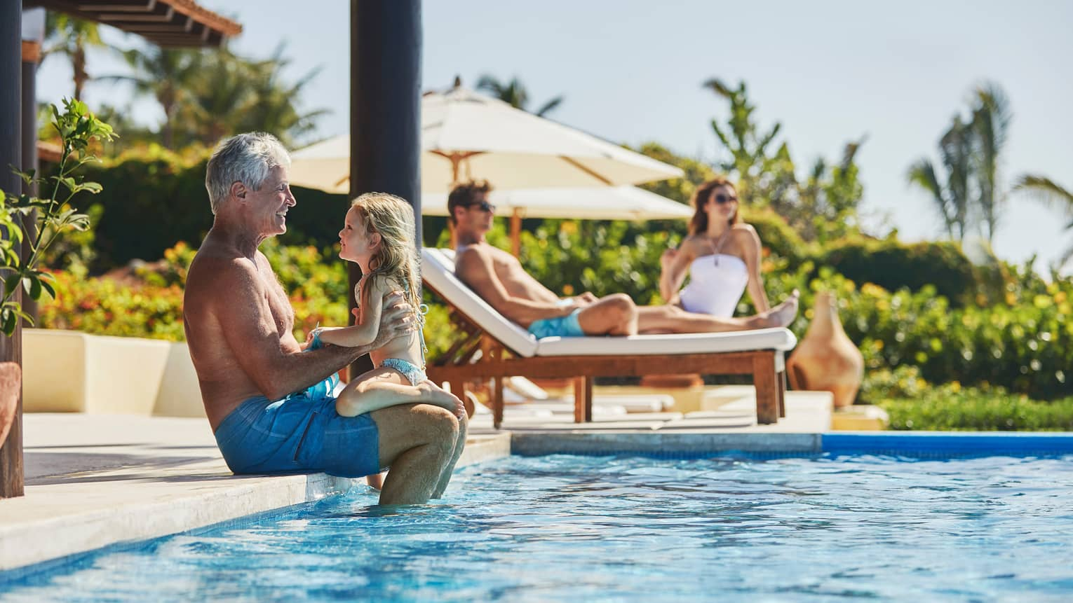 Grandfather holds young girl on edge of outdoor swimming pool, parents lounge on chairs